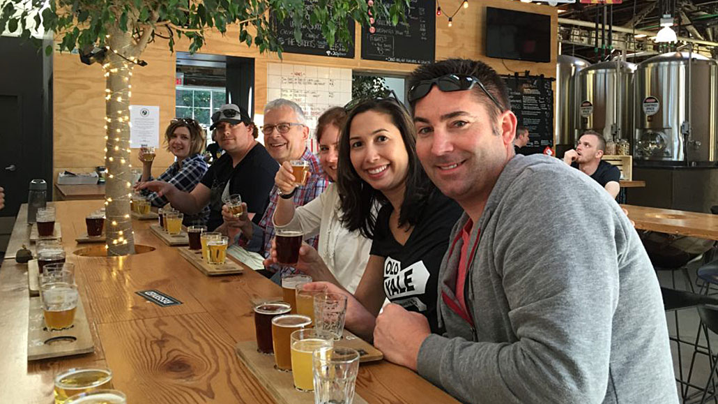Group of people sitting at a table tasting beer flights at Main St Brewery