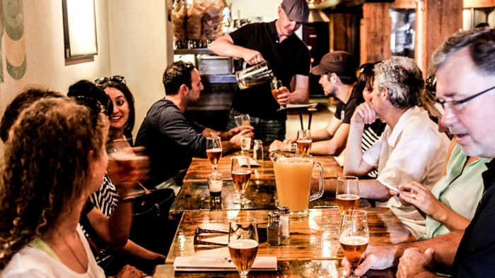 Social group of people sitting on a table for beer tasting in Gastown, Vancouver