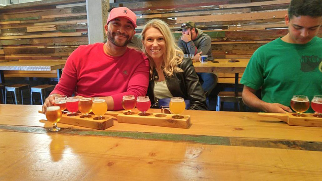 Happy couple with a beer flight on the table at Brassneck Brewery