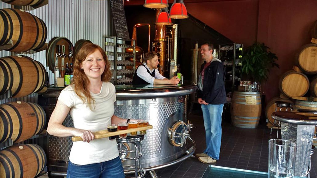 Smiling women holding a beer flight with a bar and bartender in the background