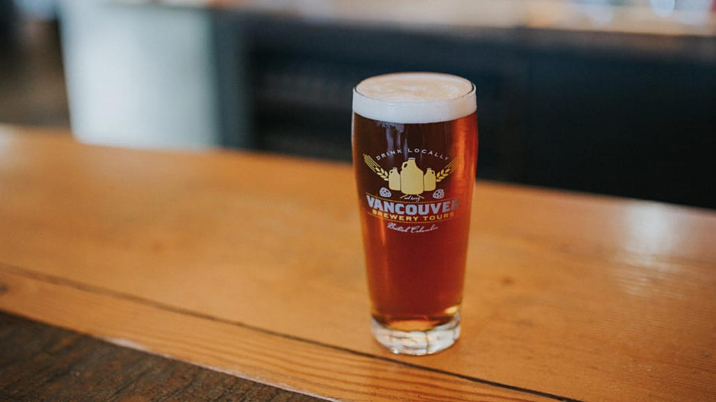 Close caption of a golden beer glass by Vancouver Brewery Tours.