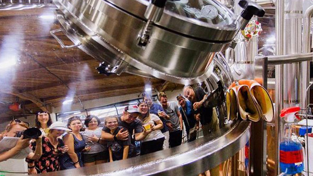 Group of people reflected from a beer tank during a beer tasting tour.