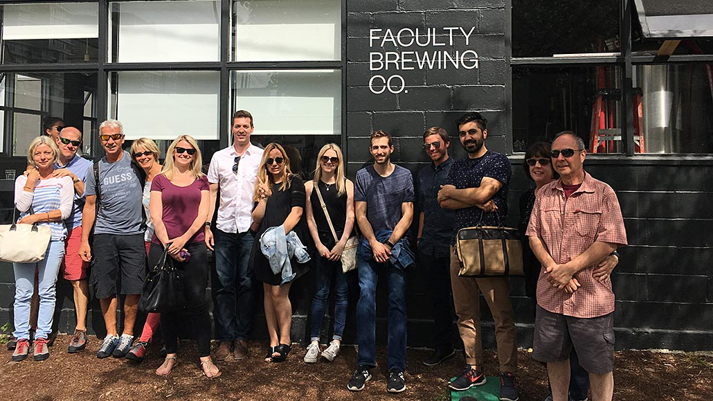 Group of people doing beer tasting tour in front of Faculty Brewing Co.