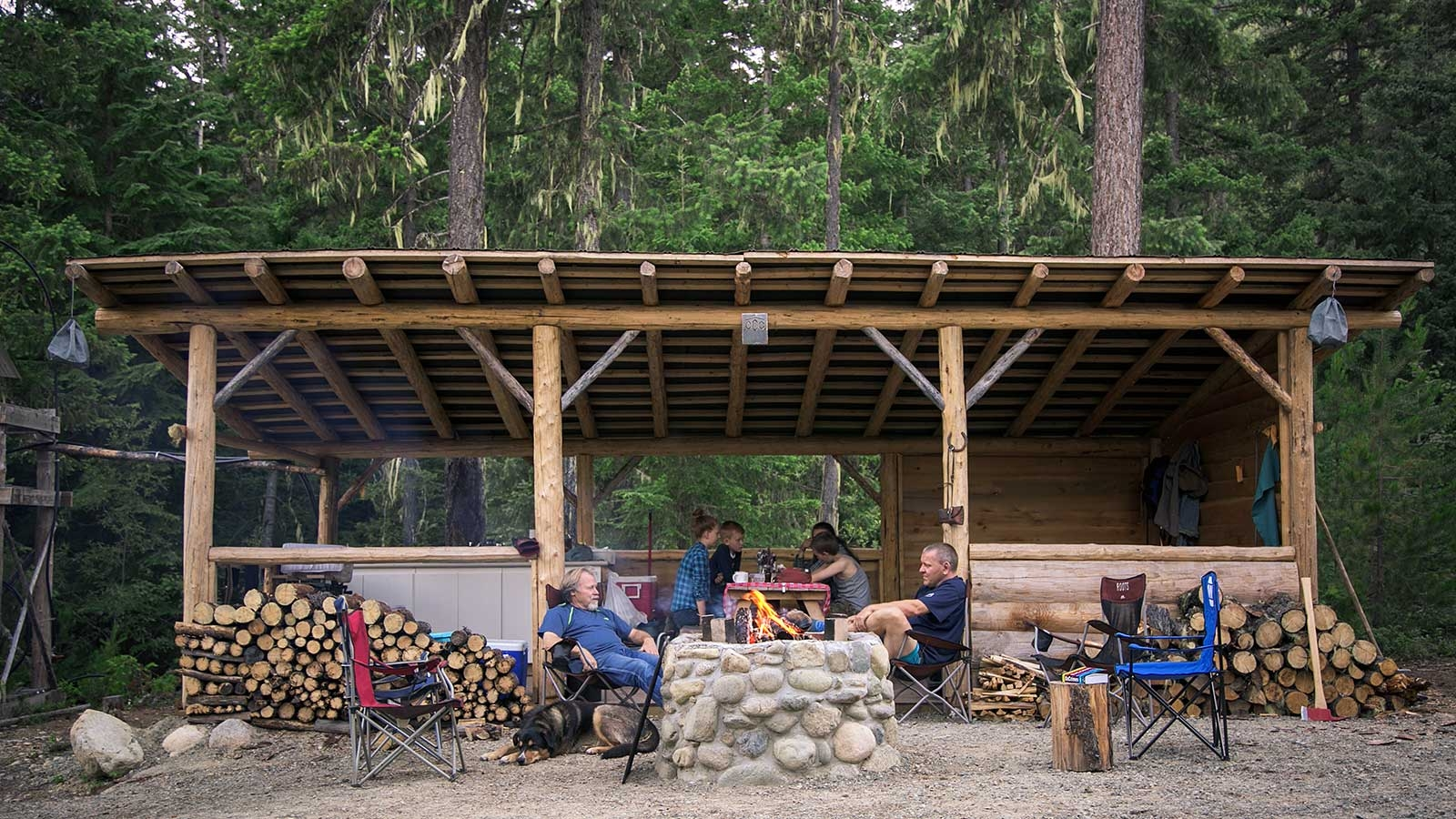 group of people relaxing at a camp fire in front of a shelter