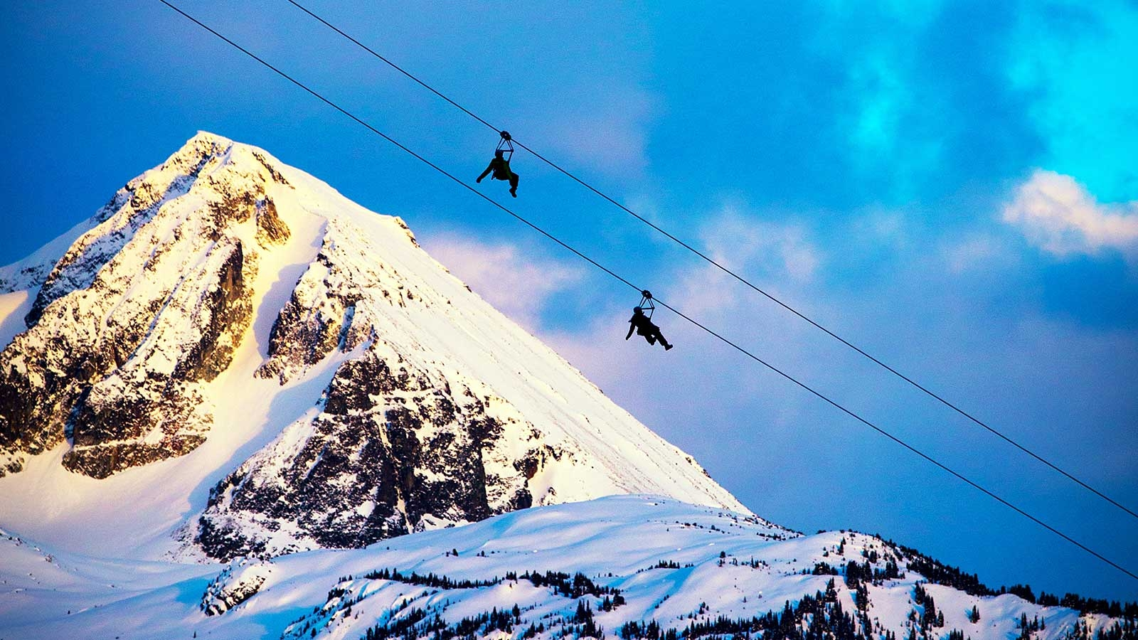 Two people ziplining with mountain top in background in Whistler