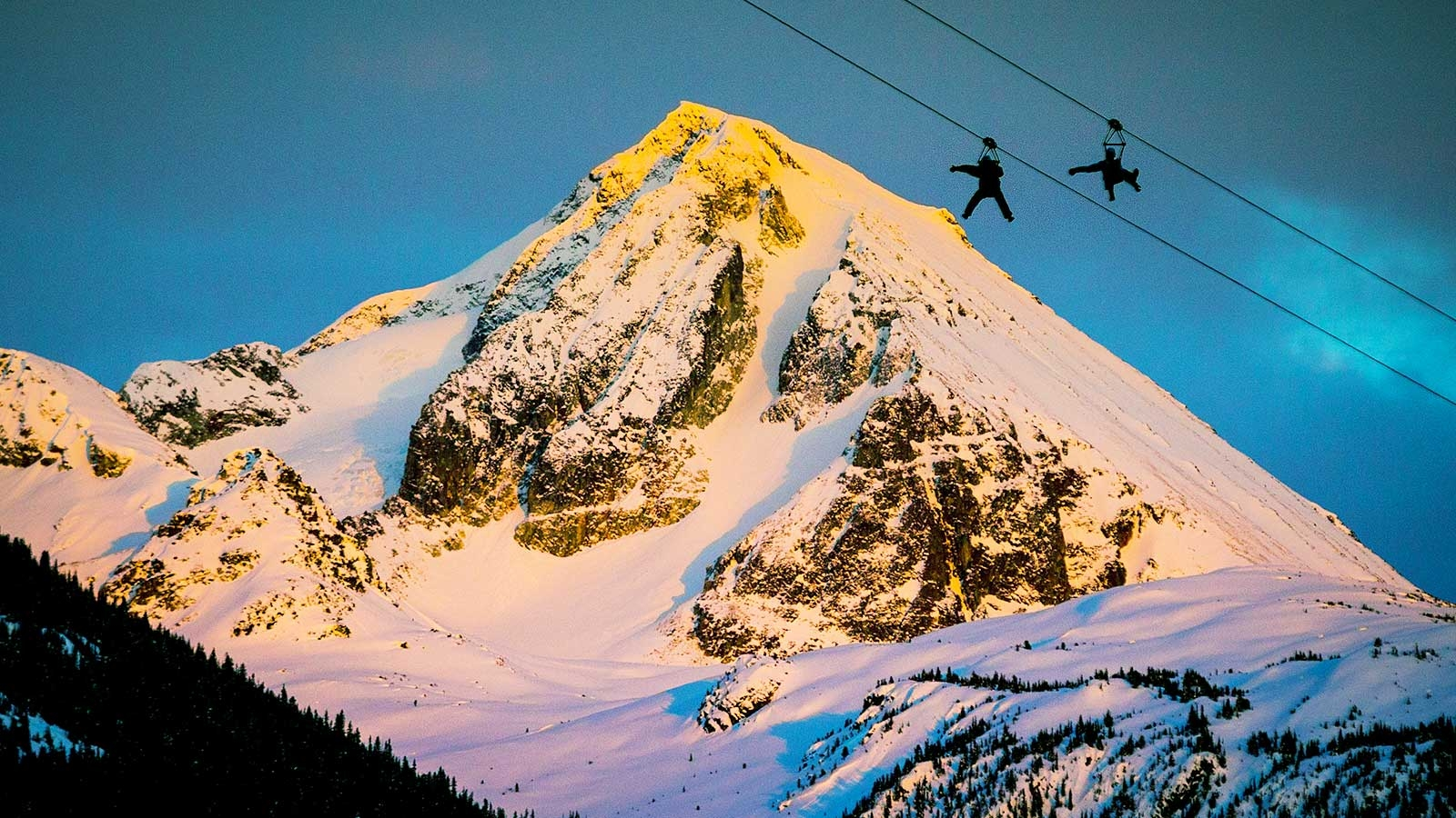 Two people ziplining with mountaintop in background with alpenglow in Whistler
