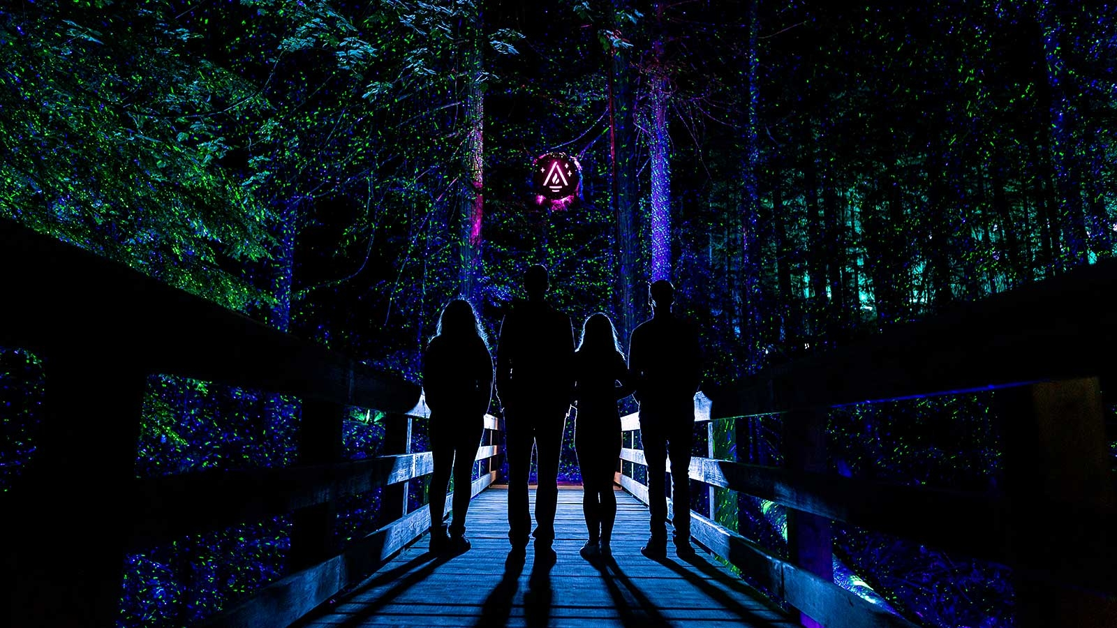 A family crossing a bridge in the dark through an illuminated forrest in Whistler