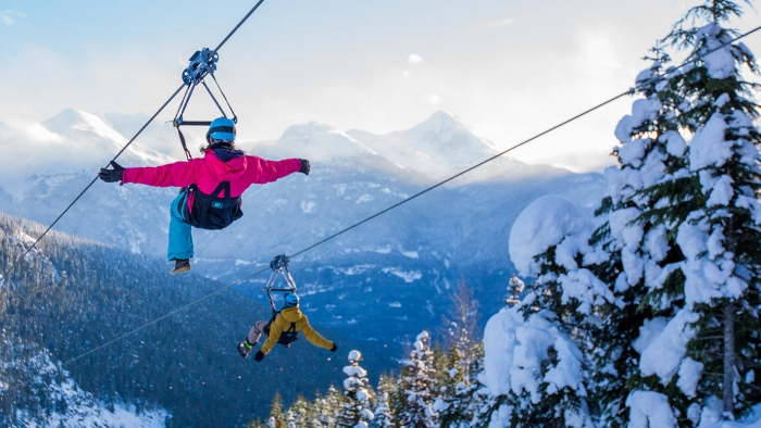 two people ziplining over snow covered trees and mountains in the background in Whistler