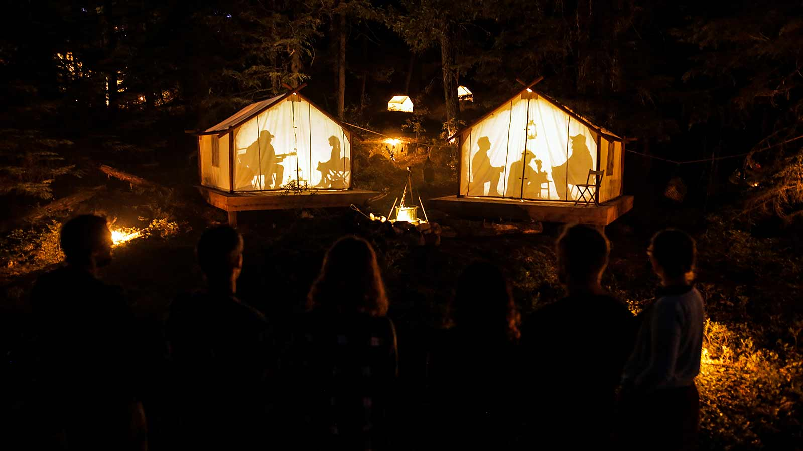 Tents in the dark with lights and persons sitting inside at Vallea Lumina Whistler Canada.