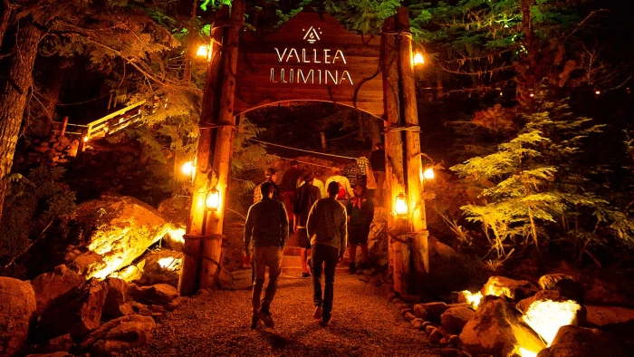 Illuminated entrance with people waling through a gate for Vallea Lumina in Whistler Canada