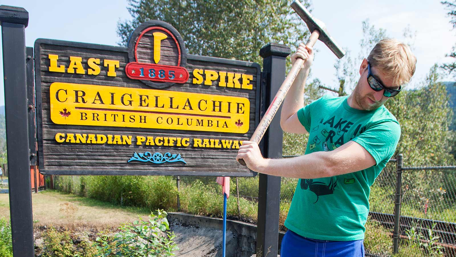 Young man standing in front of a sign in Craigellachie British Columbia Canada