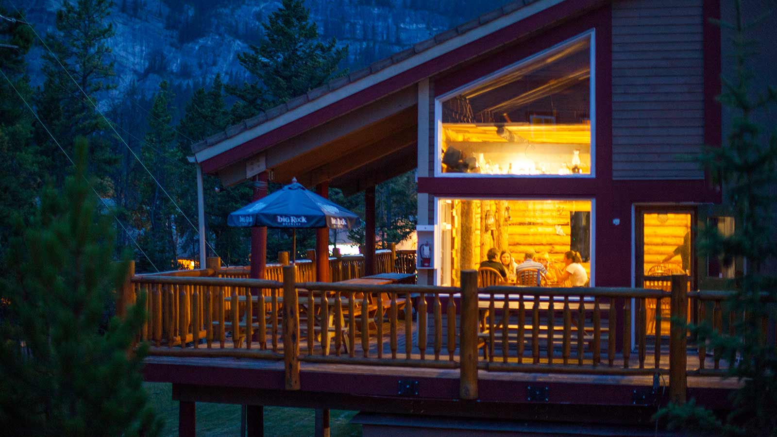 Wooden lodge with people sitting inside at HI Banff Hostel
