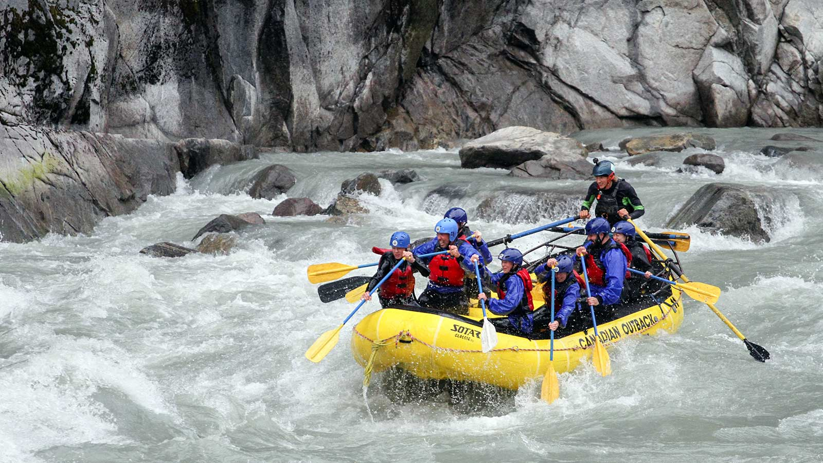 A group river rafting in a yellow raft