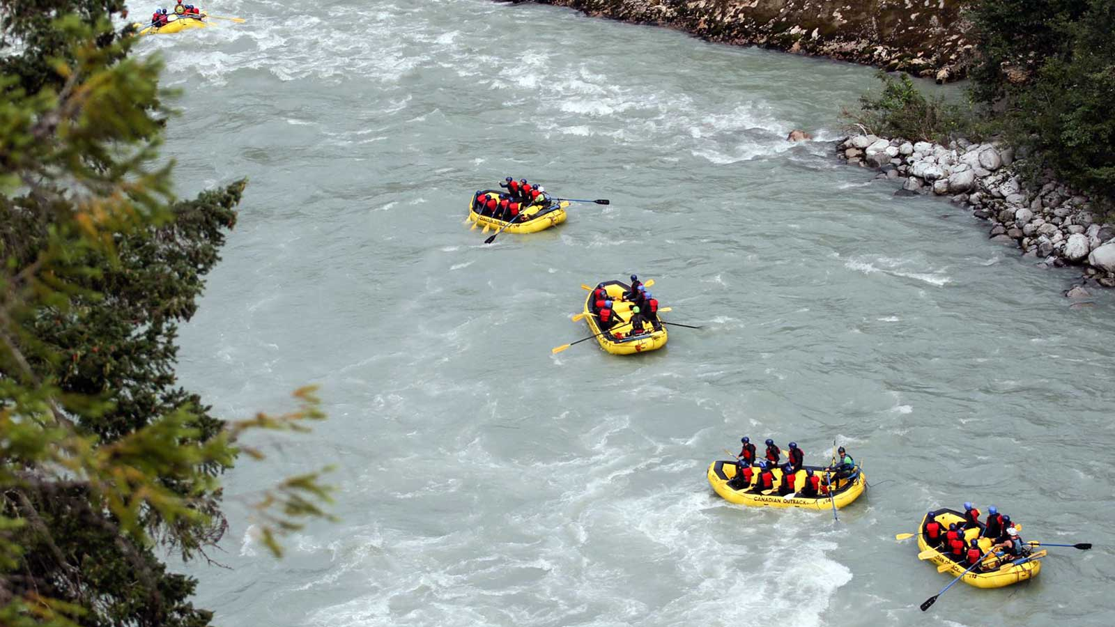 group of people river rafting in yellow boats