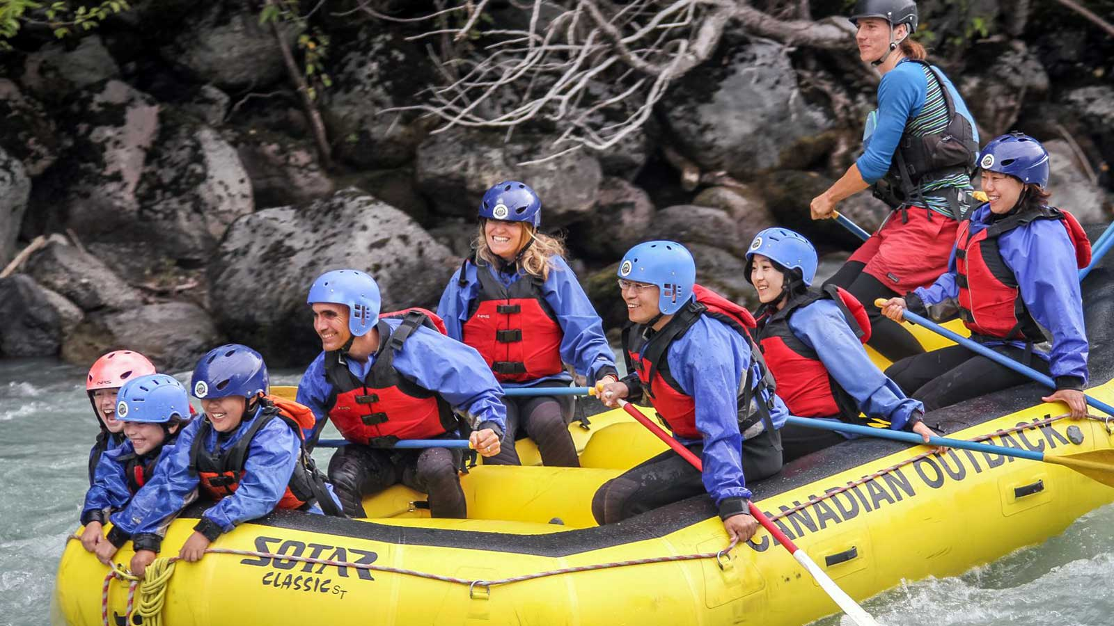 group of people river rafting in yellow boat